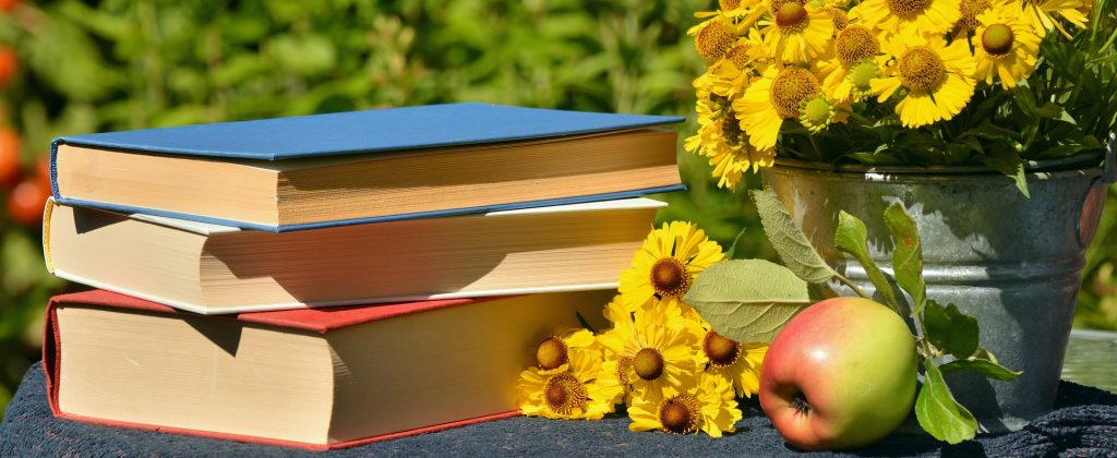 book, yellow flowers, and an apple