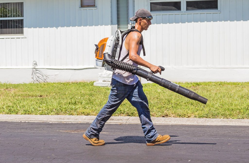 man walking wearing a leaf blower backpack